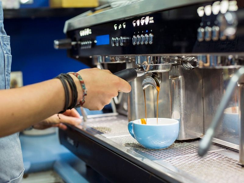 A close up of a waitress making a coffee at The Kiosk Cafe in the north marina village at Coral Sea Marina Resort