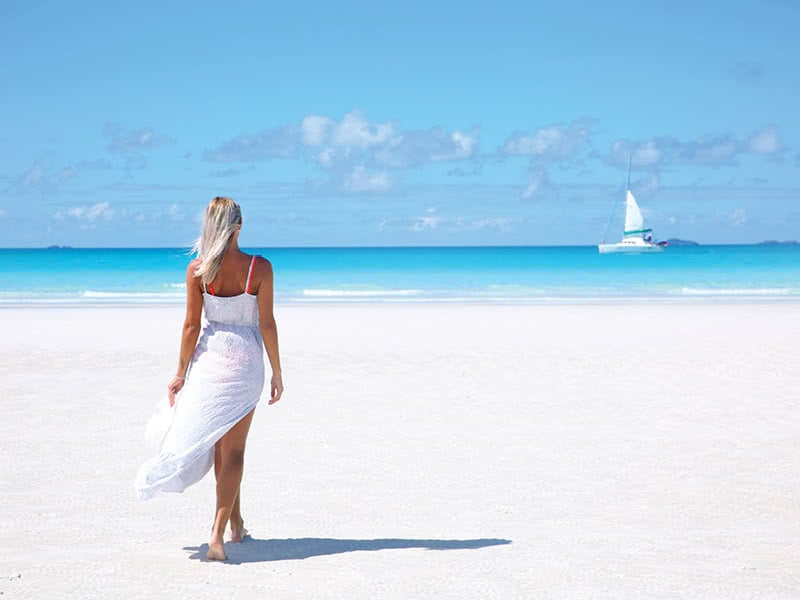 A woman walking on the white sand of Whitehaven Beach