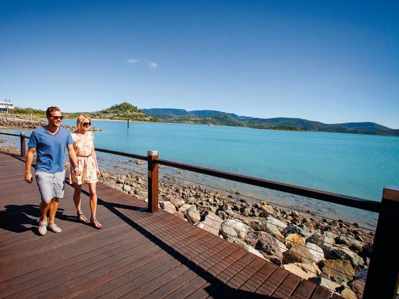A man and woman walking along the Bicentennial Walkway in Cannonvale