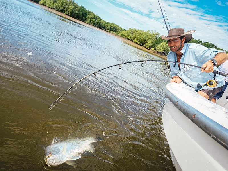 A man fishing for barramundi on a boat at Proserpine Dam