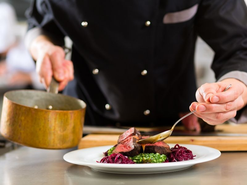 A chef pouring sauce over a meat dinner menu option