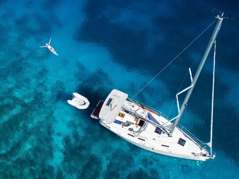 An aerial image of a woman floating on her back in the ocean next to an anchored vessel