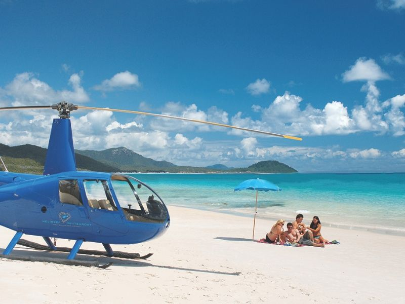 A helicopter on Whitehaven Beach with a group of friends sitting on the sand