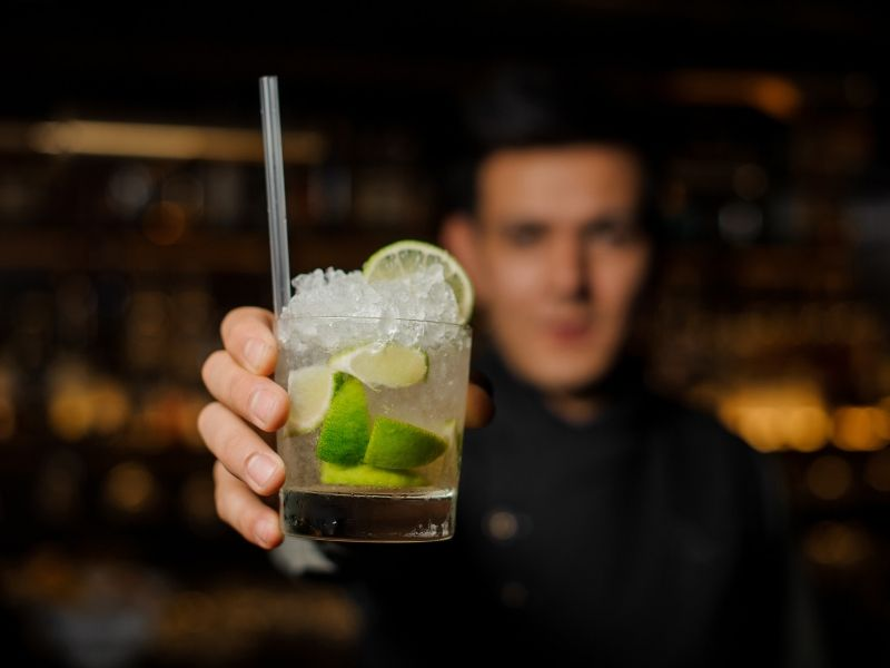 A bar tender holding a cocktail with limes and crushed ice