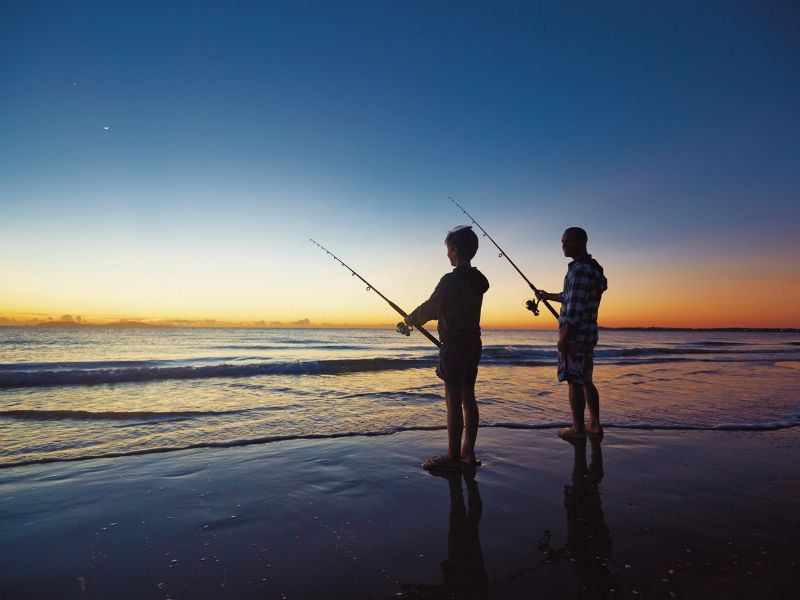 Two people fishing on the beach at sunset