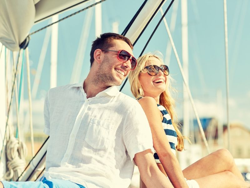 A man and woman laughing whilst sitting on a boat in a marina