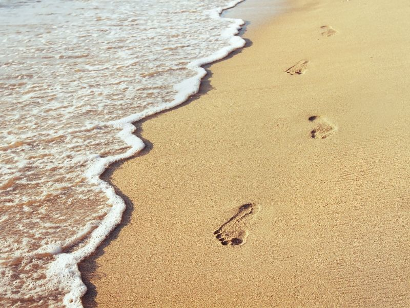 Footprints in the sand with lapping waves