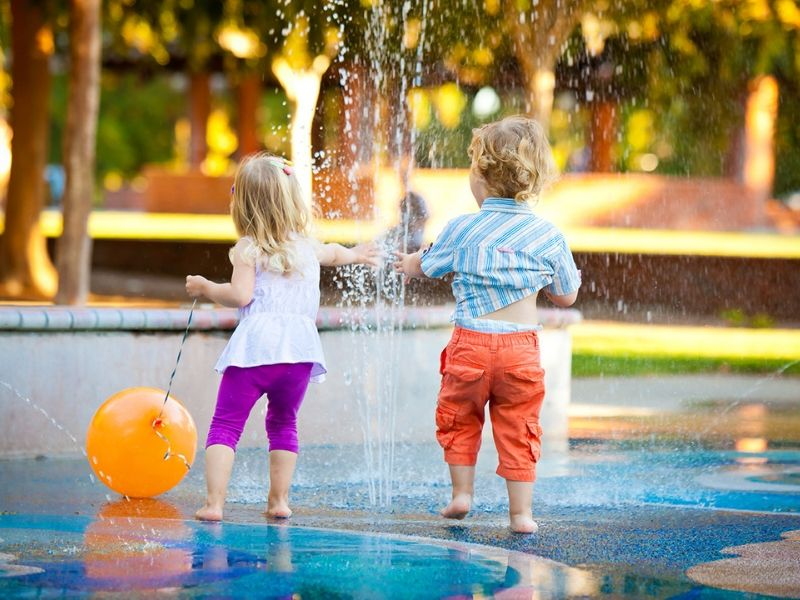 Two children playing in an outdoor small water park in a local garden