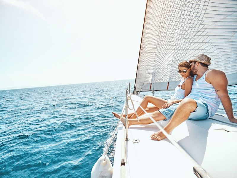 A man and woman on the bow of a sailing vessel
