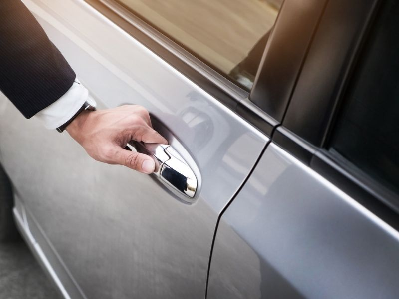 Close up image of a man's hand opening a silver car door