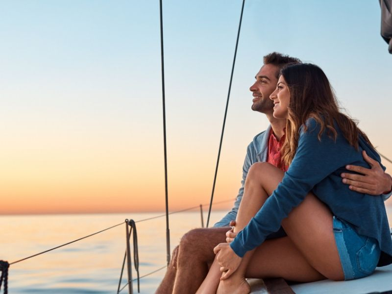 A man and woman sitting on a sailing boat at sunset