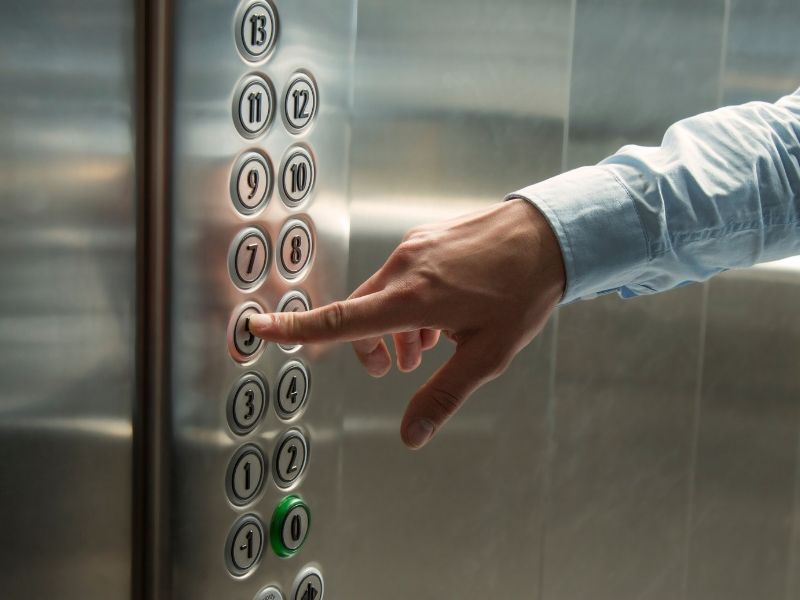 A close up image of a man pressing a button in an elevator or lift