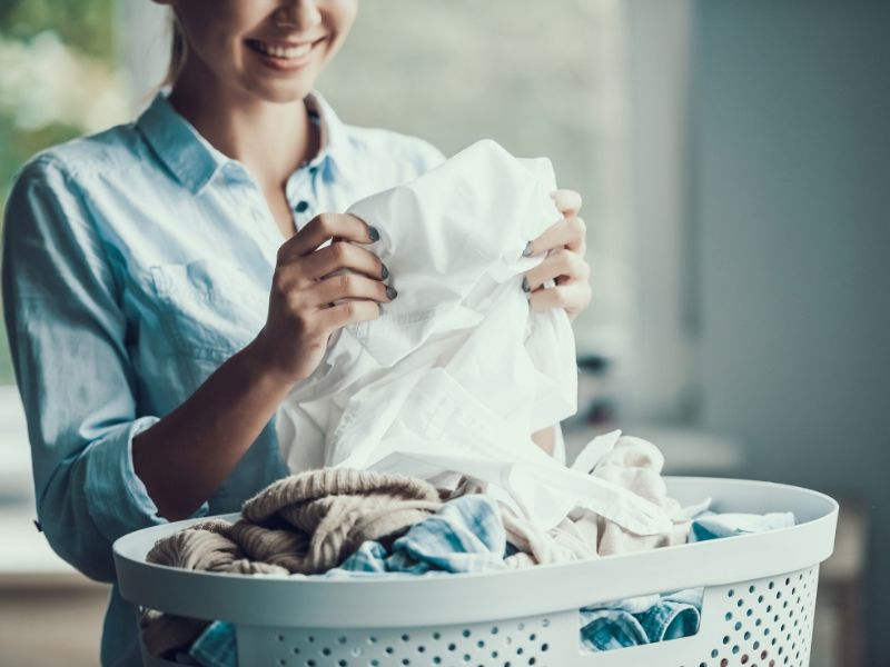 A woman folding laundry from a laundry basket at Coral Sea Marina Resort
