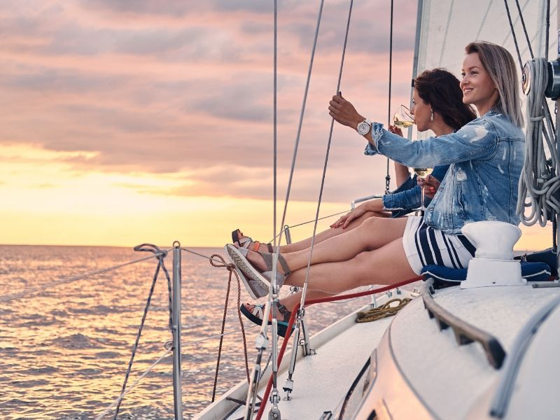 Two women on a sailing yacht at sunset