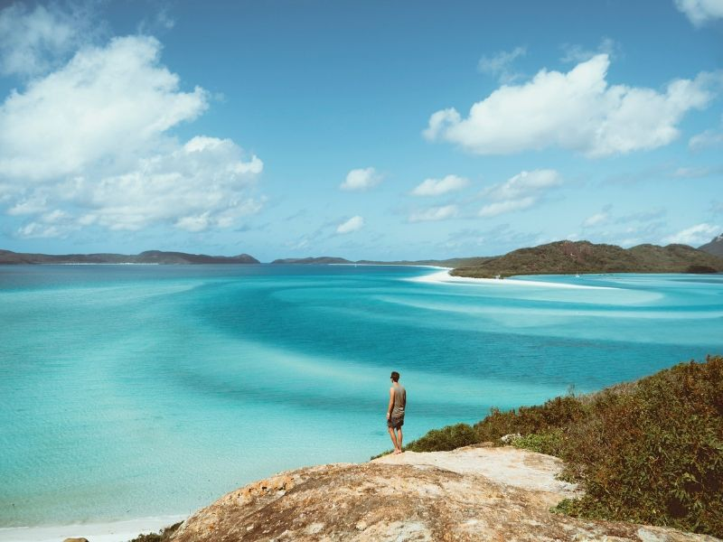 A male traveller at Hill Inlet lookout overlooking Hill Inlet and Whitehaven Beach on Whitsunday Island