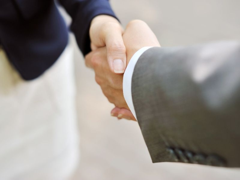 A close up image of a man and woman shaking hands