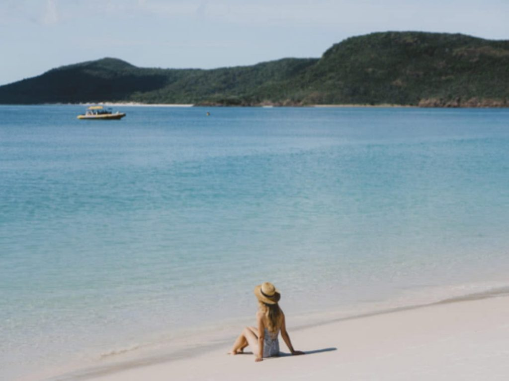 A woman sat at Whitehaven Beach on Whitsunday Island