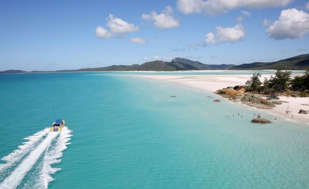 An Ocean Rafting vessel driving by Whitehaven Beach in the Whitsundays
