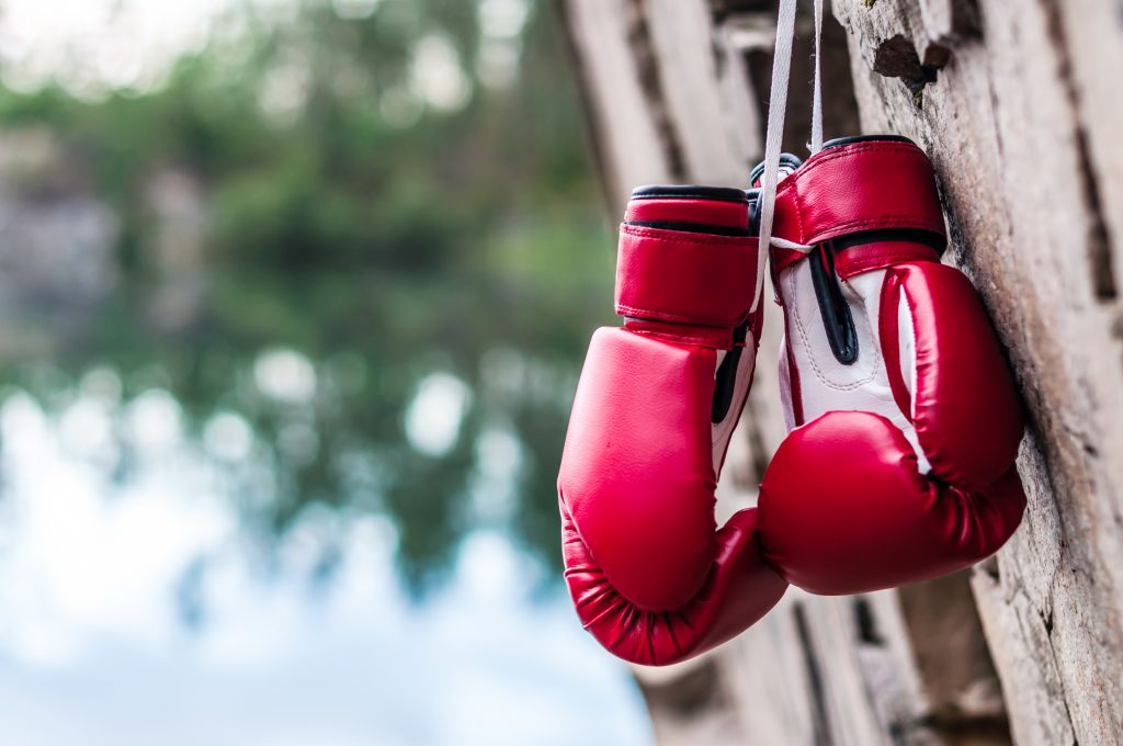 red boxing gloves suspended on a rock