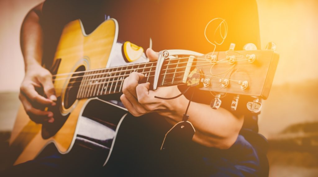 hand playing acoustic guitar, close up on musical instrument