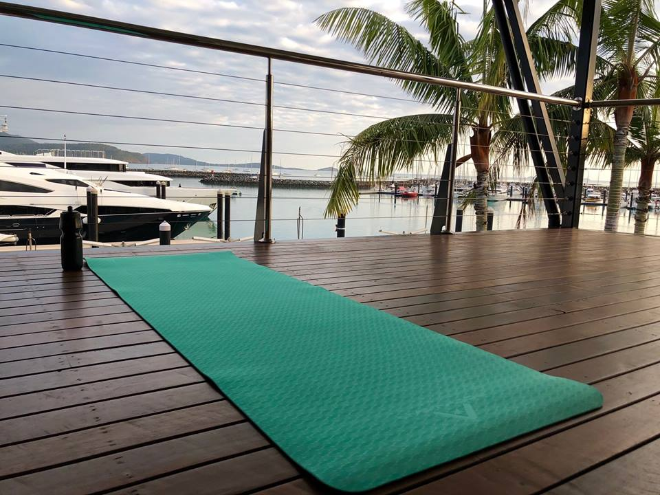 A green yoga mat on the balcony at The Lookout, located at Coral Sea Marina, with marina views