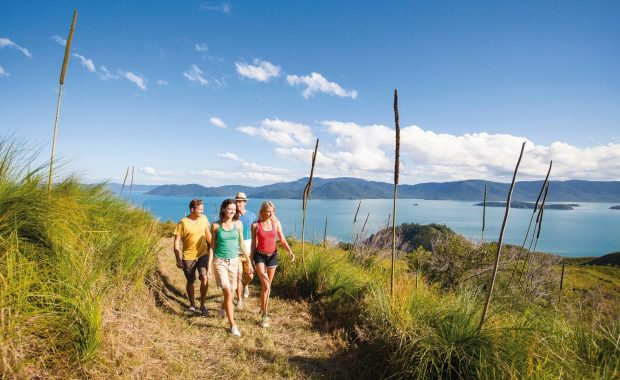 A group of friends walking the South Molle hiking trail on the Whitsunday Islands with island views