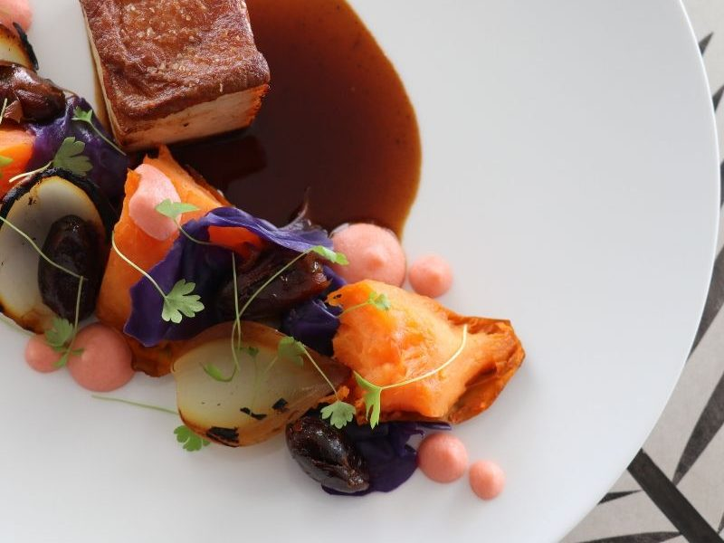 A fine dining menu option of sticky pork belly and vegetables served on a plate