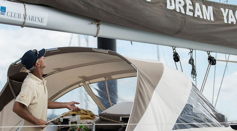 An employee at Dream Yacht Charters Australia checking the sails of a vessel at Coral Sea Marina