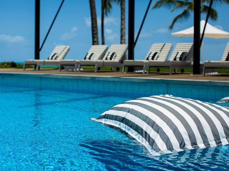 A striped floating beanbag in the pool at the Coral Sea Resort Hotel