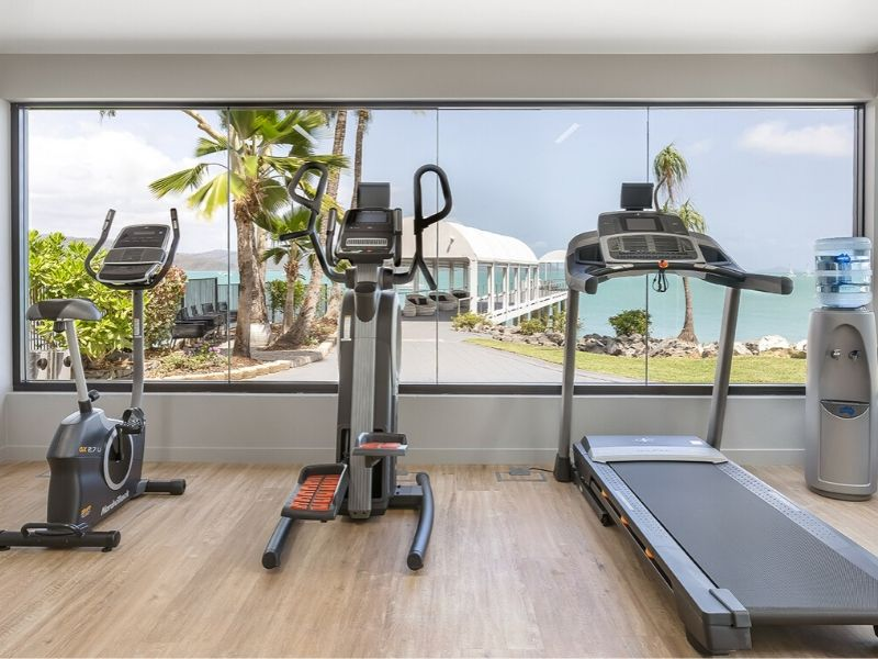 The Fitness Room, including cardio equipment and views of the private jetty and ocean, at the Coral Sea Resort Hotel