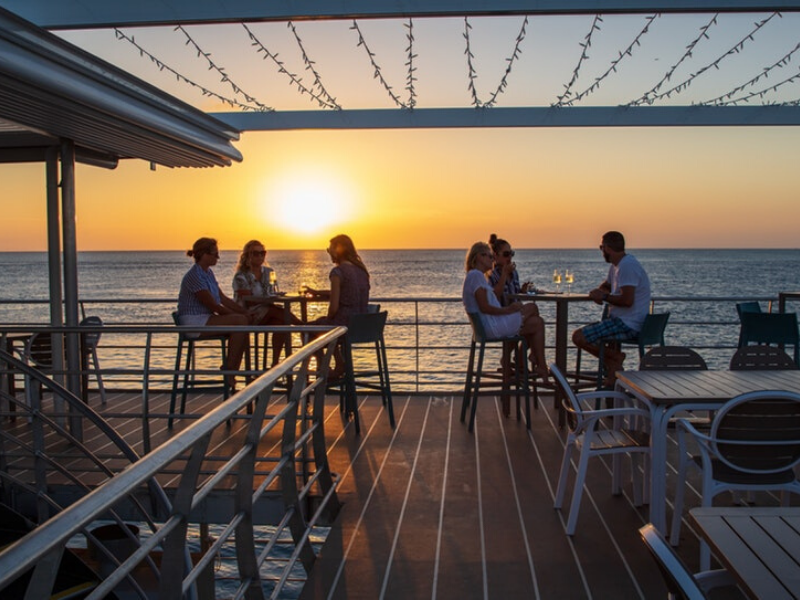 A group of people enjoying a beverage and watching the sunset on the Reefworld Pontoon with Cruise Whitsundays Reef Sleep and Reef Suites