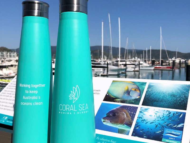 Green reusable water bottles displayed with Coral Sea Marina in the background view