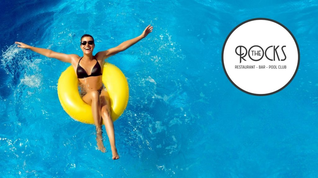 Woman in a swimming pool floating in an inflateable ring at The Rocks